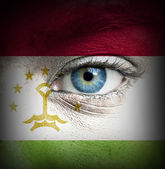 Human face painted with flag of Tajikistan — Stock Photo