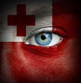Human face painted with flag of Tonga — Stock Photo