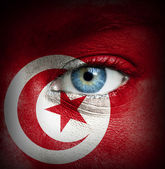 Human face painted with flag of Tunisia — Stock Photo