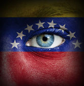 Human face painted with flag of Venezuela — Stock Photo