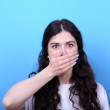Portrait of girl blushing with hand over mouth against blue back — Stock Photo