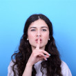 Portrait of girl with gesture for silence against blue backgroun — Stock Photo