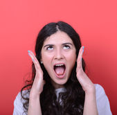 Portrait of angry girl screaming against red background — Stock Photo