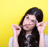 Portrait of funny girl making moustache against yellow backgroun — Stock Photo
