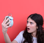 Portrait of girl in chaos looking scared at clock against red ba — Stock Photo