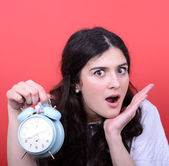 Portrait of girl in chaos looking scared at clock against red ba — Foto Stock