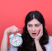 Portrait of girl looking scared at clock against red background — Stockfoto