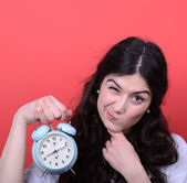Portrait of girl pointing at clock against red background — Stockfoto