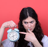 Portrait of girl pointing at clock against red background — ストック写真