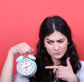 Portrait of girl pointing at clock against red background — 图库照片