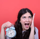 Portrait of girl screaming while holding clock against red backg — Stockfoto