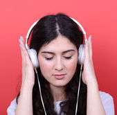 Portrait of happy teen girl dancing and listening music against — Stock Photo