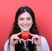 Portrait of happy woman holding heart in hands against red backg — Stock Photo
