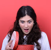 Portrait of happy woman opening gift box against red background — Stock Photo