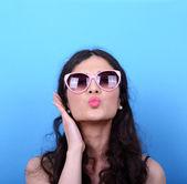 Portrait of woman with retro glasses sending kiss against blue b — Stock Photo