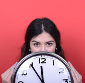 Portrait of girl holding huge office clock against red backgroun — Stock Photo