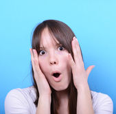 Portrait of girl with shock gesture against blue background — Stock Photo