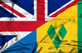 Waving flag of Saint Vincent and Grenadines and UK — Stock Photo