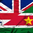 Waving flag of Suriname and UK — Stock Photo