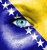 Woman face painted with flag of Bosnia and Herzegovina — Stock Photo