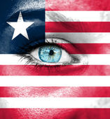 Woman face painted with flag of Liberia — Stock Photo