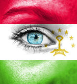 Woman face painted with flag of Tajikistan — Stock Photo