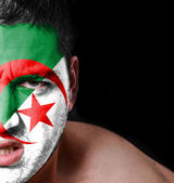 Portrait of angry man with painted flag of Algeria — Stock Photo