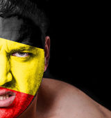 Portrait of angry man with painted flag of Belgium — Stock Photo