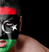 Portrait of angry man with painted flag of Libya — Stock Photo