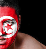 Portrait of angry man with painted flag of Tunisia — Stock Photo