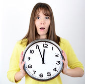Portrait of a young female holding big clock against white backg — Stock Photo