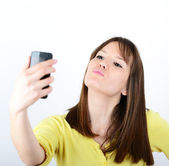 Beautiful woman taking selfies against white background — Stock Photo