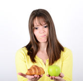 Doubtful woman holding an apple and croissant trying to decide w — Stock Photo