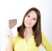 Young woman eating chocolate bar against white background — Stock Photo