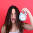 Portrait of sleepy young female in chaos holding clock against r — Stock Photo
