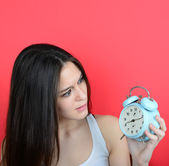 Portrait of girl in chaos looking scared at clock against red ba — Stok fotoğraf