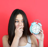 Portrait of girl in chaos looking scared at clock against red ba — Stockfoto