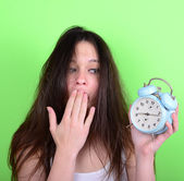 Portrait of sleepy young female in chaos holding clock against g — Stok fotoğraf