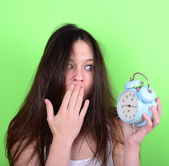 Portrait of sleepy young female in chaos holding clock against g — Stockfoto