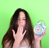 Portrait of sleepy young female in chaos holding clock against g — ストック写真
