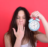 Portrait of sleepy young female in chaos holding clock against r — 图库照片