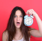 Portrait of sleepy young female in chaos holding clock against r — Stockfoto