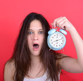 Portrait of sleepy young female in chaos holding clock against r — Foto de Stock