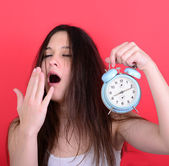 Portrait of sleepy young female in chaos holding clock against r — ストック写真