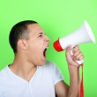 Portrait of young man shouting with a megaphone against green ba — Stock Photo #47946501