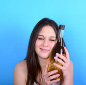 Portrait of young female having hangover with bottle pf alcohol — Stock Photo