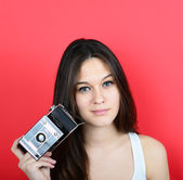 Portrait of young female holding vintage camera against red back — Stock Photo