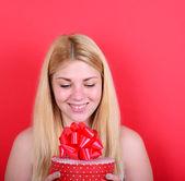 Portret van gelukkig vrouw cadeau doos tegen rode achtergrond — Stockfoto