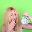 Portrait of sleepy young female in chaos holding clock against g — Stock Photo