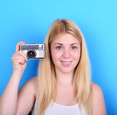 Portrait of young female holding vintage camera against blue bac — Stock Photo